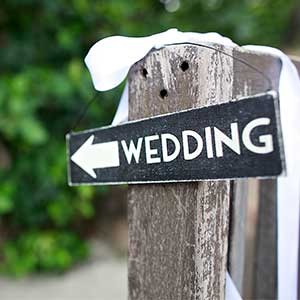 wedding sign attached to a rustic fence post