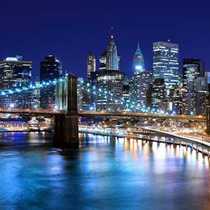 New York city at night with Brooklyn Bridge lit up in foreground