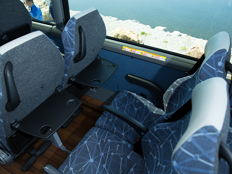 comfortable bus seats with armrests and tray tables and footrest