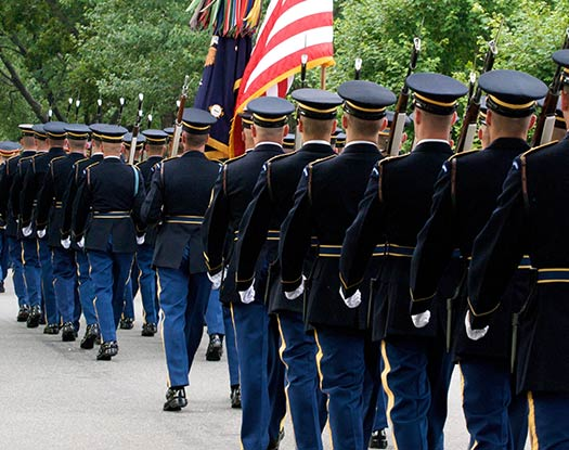 military people in marching formation with American flag